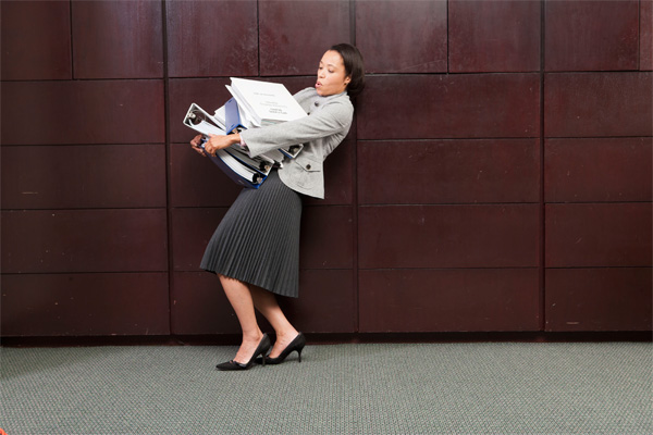 Woman struggling to hold binders as she walks.