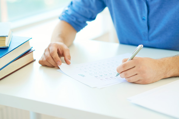 A man sitting at a white table filling out a moving checklist.