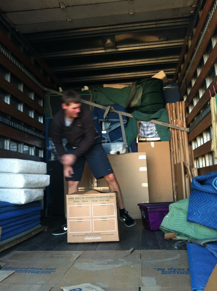 A man inside of a moving truck with large boxes and tarps.