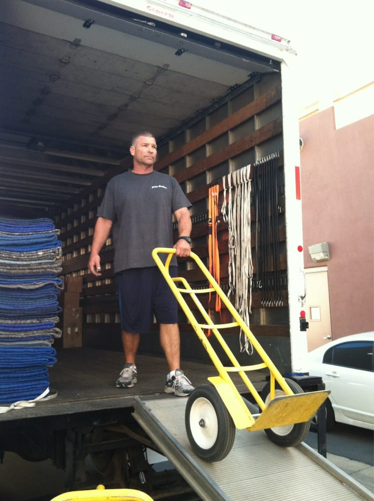 A man standing on a moving truck ramp with a yellow moving dolly.
