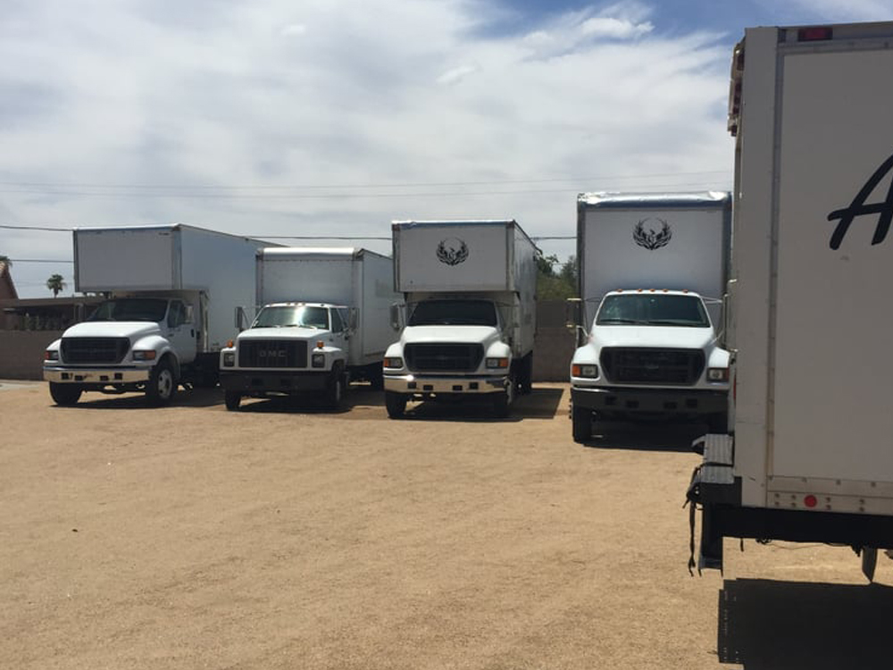 Five Arizona Brothers Moving Company trucks parked in a dirt lot.